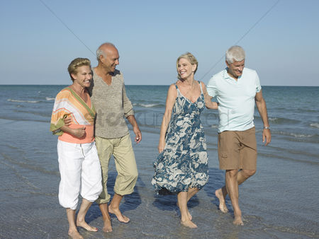 Appearance : Two senior couples walking barefoot on beach