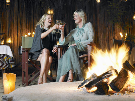 Toasting : Two women sitting by bonfire at outdoor nightclub toasting