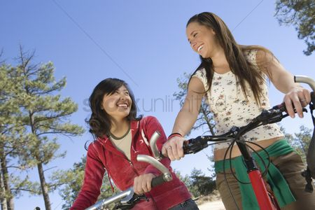 Women group outside : Two women stand smiling with mountain bikes