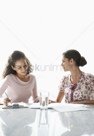 Curly hair : Two young women sitting at table writing on paper