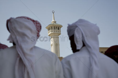 Religion : Uae dubai group of traditionally dressed muslim men perform a song for visitors to the bastakia