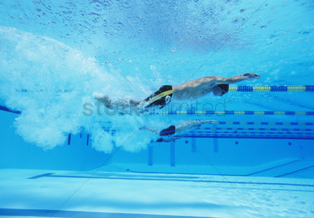 Swimmer : Underwater shot of three male athletes racing in swimming pool