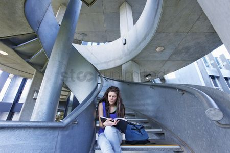 Three quarter length : University student reading on staircase