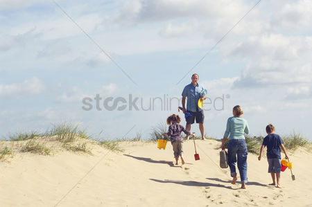 Summer : Vacationing family walking up sand dune on beach back view