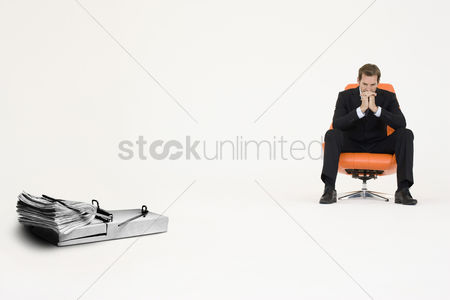 Worry : Wad of cash on mouse trap with pensive businessman on chair representing financial difficulties
