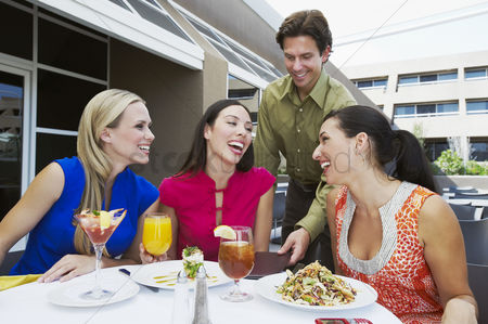 Food  beverage : Waiter bringing check to women in restaurant