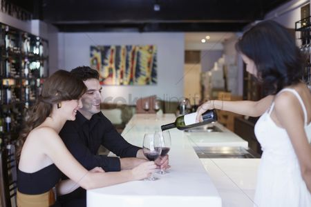 Wine bottle : Waitress pouring wine for man and woman at the bar