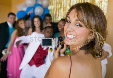 High school : Well-dressed teenager girl video taping friends at school dance
