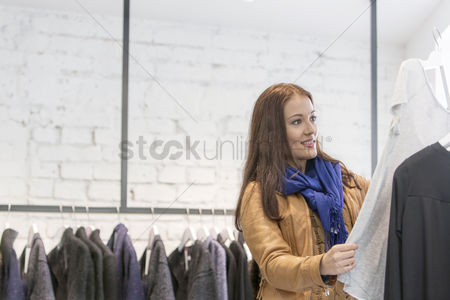 Shopping background : Woman analyzing top in store