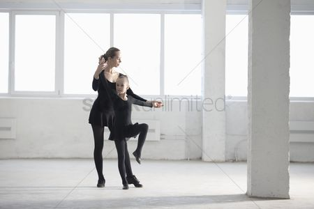 Teacher : Woman and girl practise dance moves