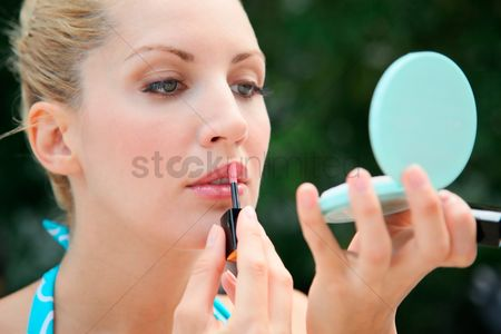 Eastern european ethnicity : Woman applying lip gloss while looking at compact mirror