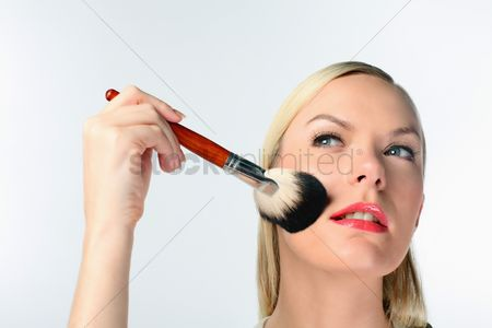 British ethnicity : Woman applying make-up on her face