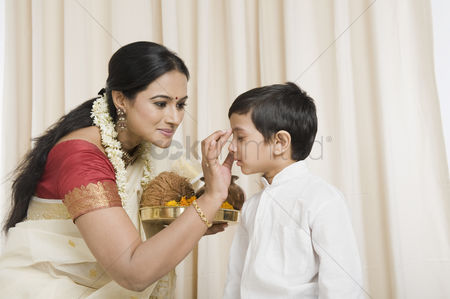 Respect : Woman applying tilak to her son