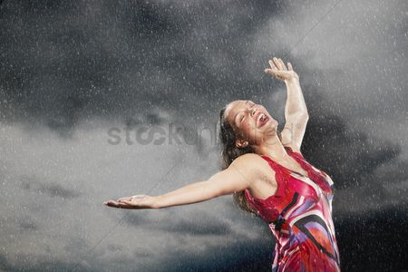 Cloud : Woman arms outstretched smiling standing in rain