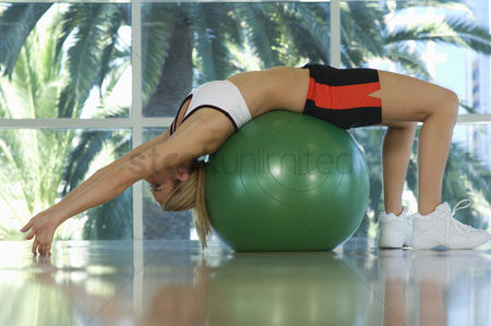 Workout : Woman bending backwards over exercise ball