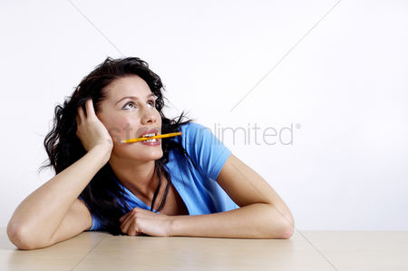 Thought : Woman biting a pencil while thinking