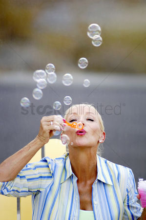 Enjoying : Woman blowing soap bubbles