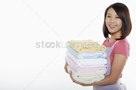 Malaysian : Woman carrying a stack of clean towels