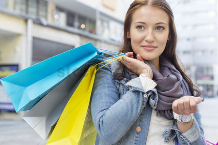 Young woman : Woman carrying shopping bags while looking away