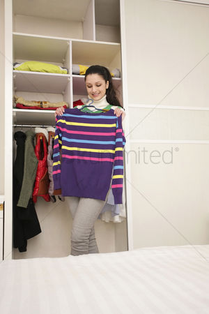 Cold temperature : Woman choosing warm clothing from her wardrobe