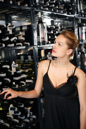 Sets : Woman choosing wine in the wine cellar