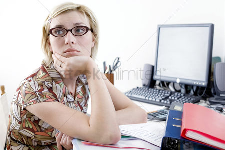 Lady : Woman daydreaming at desk in a home office
