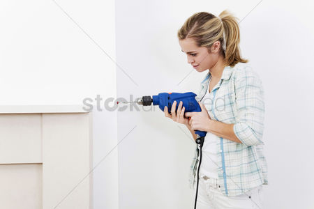 Fixing : Woman drilling the wall