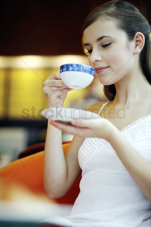 Satisfaction : Woman enjoying a cup of aromatic coffee in a cafe