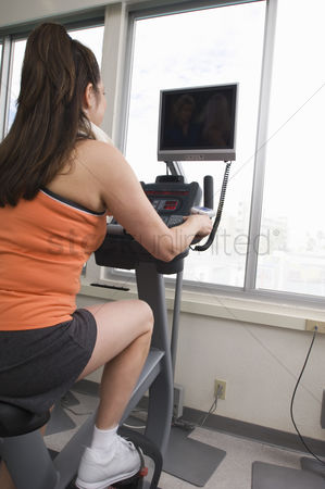 Workout : Woman exercising on a stationary bike with a tv