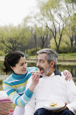Having fun : Woman feeding her husband while picnicking in the park