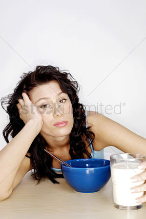 Frowning : Woman getting bored with her breakfast