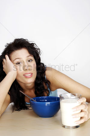 Frowning : Woman having breakfast with her head resting on her hand