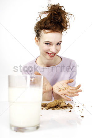 Satisfying : Woman having cookies and a glass of milk for breakfast