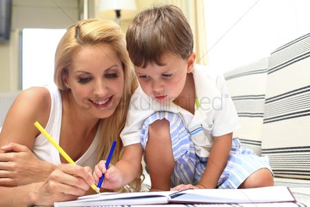 Eastern european ethnicity : Woman helping son to colour in book