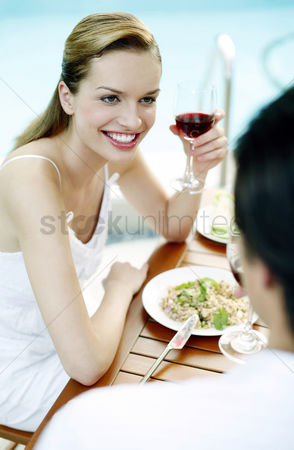 Celebrating : Woman holding a glass of red wine while talking to her boyfriend