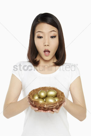 Amazed : Woman holding a nest filled with gold eggs  looking shocked
