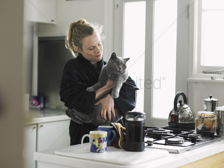 Ponytail : Woman holding cat standing in kitchen
