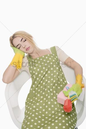 Housewife : Woman holding cleaning products while sleeping on the chair