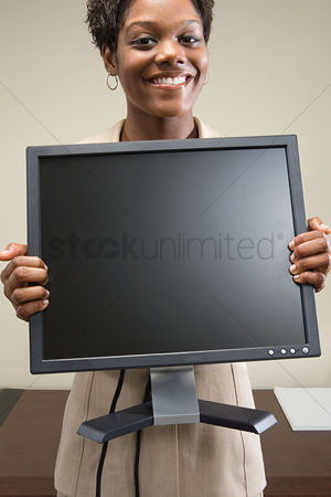 Interior : Woman holding computer monitor