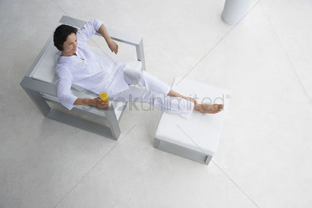Modern lifestyle : Woman holding glass of juice reclining in armchair elevated view
