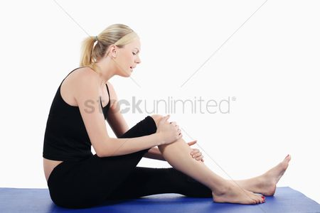 Young woman : Woman holding her knee while sitting on yoga mat