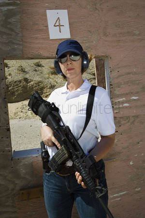 Firing : Woman holding machine gun at firing range portrait