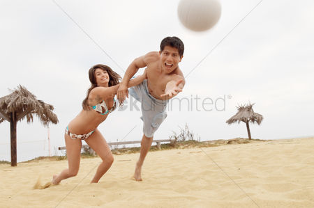 Diving : Woman holding man back from diving for volleyball on beach