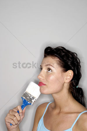 Paint brush : Woman holding paint brush thinking