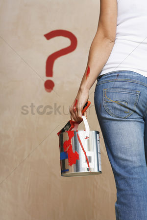Denim : Woman holding painting can facing wall with painted question mark mid section back view