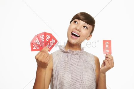 Shopping background : Woman holding sale signs and thinking
