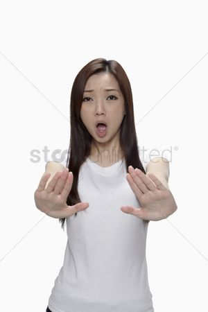 Frowning : Woman holding up both hands to signal stop