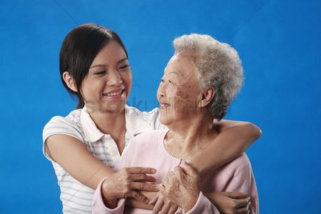 Aging process : Woman hugging senior woman from the back