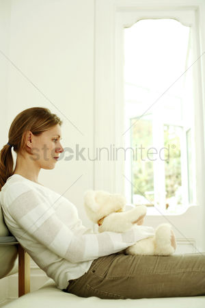 Three quarter length : Woman hugging teddy bear while daydreaming