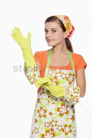Housewife : Woman in apron putting on rubber glove